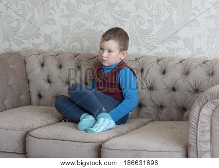 the boy with a sad kind of sitting on the couch