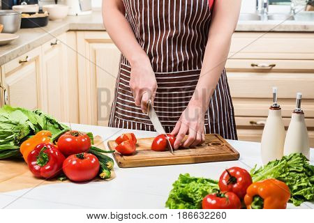 Young woman cooking in the kitchen at home. Healthy food. Diet. Dieting concept. Healthy lifestyle. Cooking at home. Prepare food. A woman cuts a tomato and vegetables with a knife.
