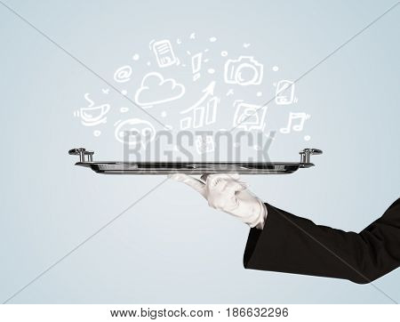 A professional waiter holding a silver plate with drawn communication, business and online media icons in front of a light blue background