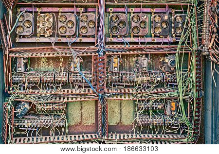 Old broken switchboard in interior of destroyed manufacturing plant