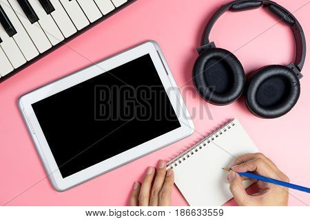 Music Songwriter is writing on a notebook with blank tablet screen for music application mock up