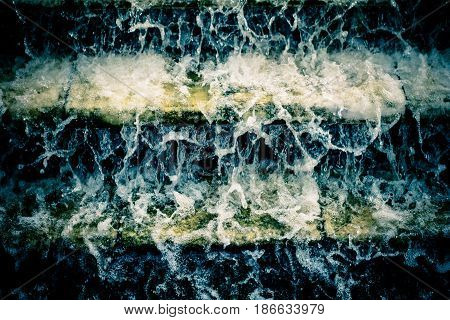Water flows turbulent flow the stairs. Foaming water.
