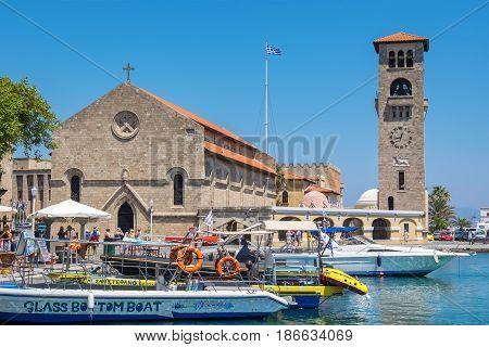 RHODES GREECE - JULY 4 2015: Tourists walking on quay of Mandraki harbour near Church of the Evangelismos (Annunciation)