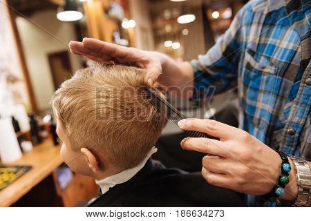 From the top of the head. Nice pleasant professional barber holding a comb and combing the boys hair while standing behind him