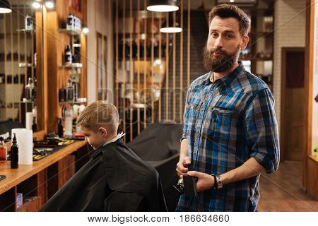 Pleasant job. Nice good looking bearded hairdresser holding a comb and preparing to work while being in the barbershop