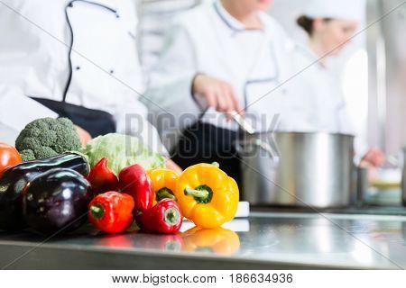 Team of chefs preparing food in canteen kitchen