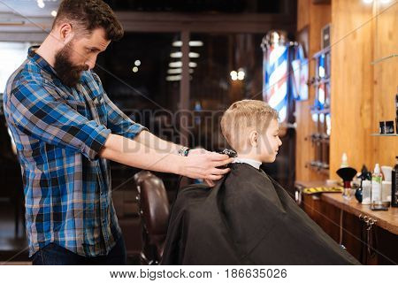 Perfect symmetry. Pleasant nice experienced hairdresser using the haircutting machine and doing the haircut while standing behind the boy