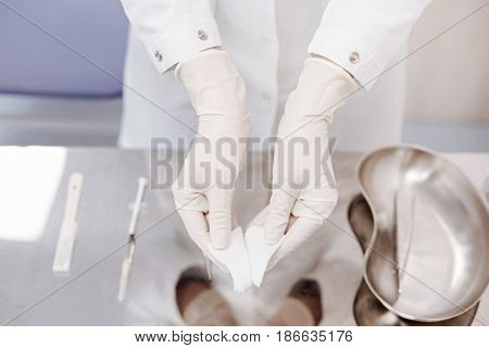 Everything is sterile. Close up of a nice professional doctor wearing disposable gloves and holding pieces of bandage while standing over the table