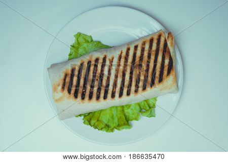 Shaurma grilled with chicken, French fries on a salad leaf. fast food