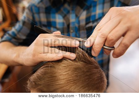 Perfect hairstyle. Close up of ends of the hair being cut by a nice professional experienced hairdresser while doing his job