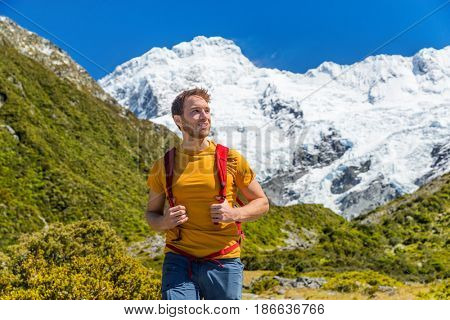 Hiking man in New Zealand mountains on Mt Cook trail with snow capped mountain peaks. Happy hiker walking in nature landscape.
