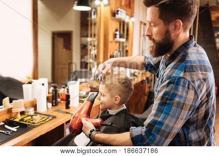 I like it. Positive happy cute boy wearing a cope and looking in the mirror while watching how his haircut is done