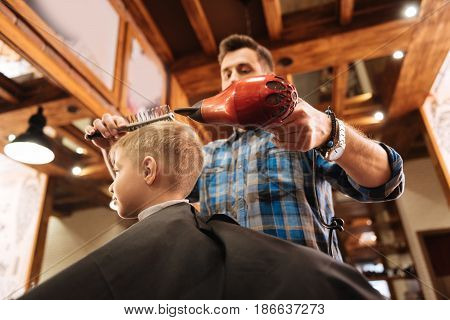 Being fashionable. Pleasant nice experienced hairdresser holding a hair dresser and using a brush while modeling his clients hair