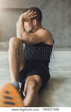 Young man sit-ups and cross crunches for abs, workout in fitness club. Portrait of caucasian guy making exercise, muscles, training indoors