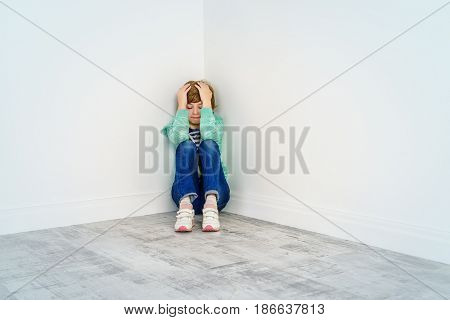Portrait of a sad nine year old girl sitting in the corner with her face in her hands.