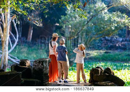 Family outdoors visiting ancient Preah Khan temple in Angkor Archaeological area in Cambodia