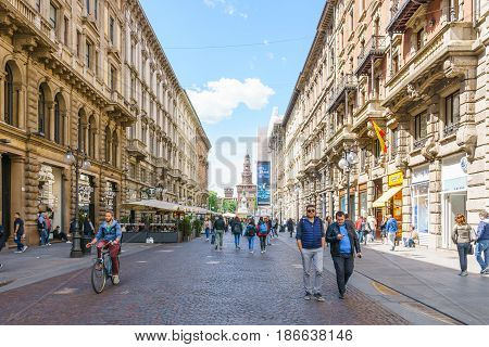 Milan Italy - April 28 2017: Daytime of architecture of the via Dante of Milan and a tourist on street with Sforzesco Castle in a background with blue sky in Milan Italy.