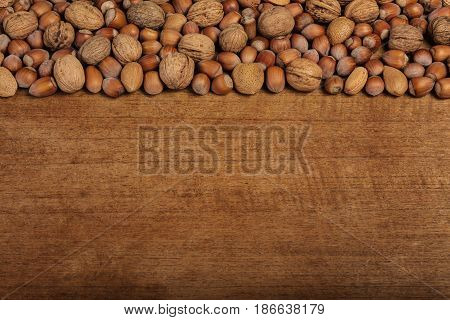 Variation of walnuts and hazelnuts on a wooden background