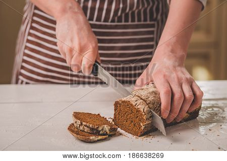 Woman cutting bread on wooden board. Bakehouse. Bread production. A woman in a striped apron