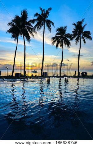 Beautiful sunset on tropical beach with palm silhouettes