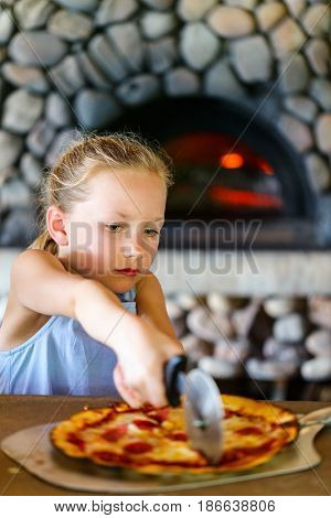 Adorable little girl eating pizza for lunch