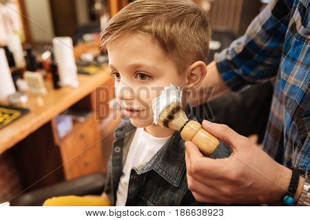 I am a grownup. Nice pleasant cute boy having some foam on his cheek and having his first shaving while being in the barbershop