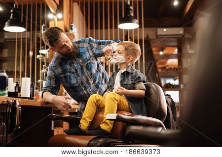 For shaving. Professional nice male barber using a shaving foam and holding a brush while shaving his client