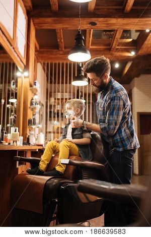 In the barbershop. Positive handsome nice barber standing behind the boy and shaving him while doing his job