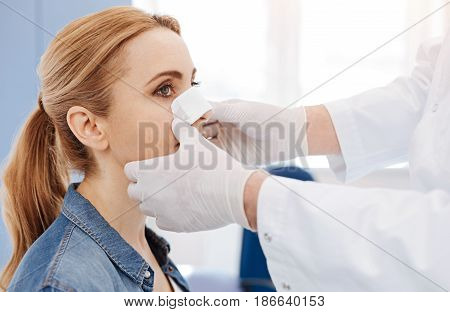 Cosmetic surgery. Nice professional male doctor wearing disposable gloves and standing in front of his patient while putting a medical dressing on her nose