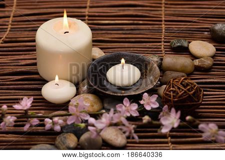 Pink cherry ,stones, candle, on mat background