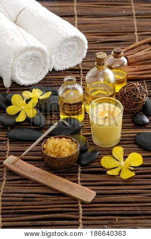 spa setting on mat background with yellow orchid, towel