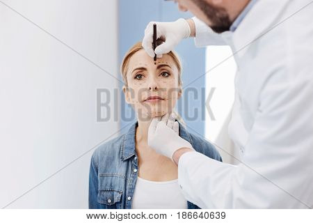 Beautiful face. Professional handsome male doctor holding a highlighter and drawing correction lines on his patients face while preparing her to the cosmetic surgery
