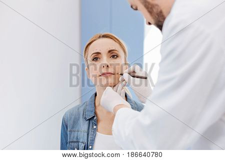 Face surgery. Professional male plastic surgeon looking at his patients face and drawing correction lines on it while preparing to a face surgery