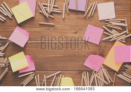 Stationery - top view flat lay shot of many multicolored blank sticky and memo notes and color pencils made round frame on wooden table background, copy space, nobody, objects
