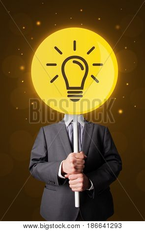 Smart businessman holding round sign with yellow lightbulb