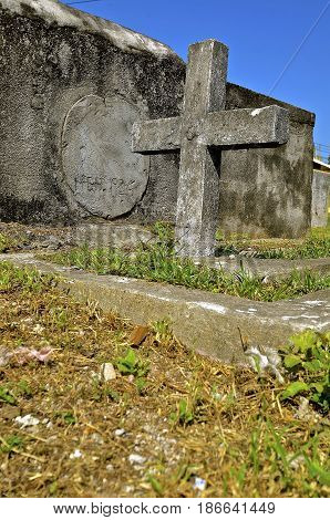 A  very old cross and tomb in an unkept cemetery is in memory of an unknown person