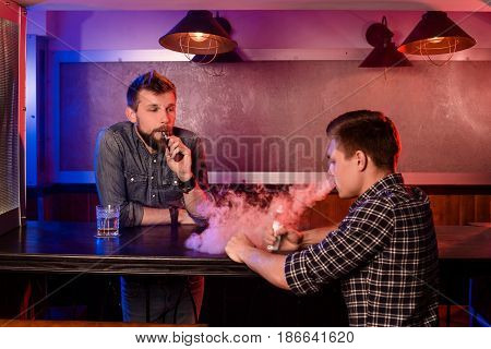 Vaping man holding a mod. A cloud of vapor at the vapebar. Two men rest in a bar and smoke electronic cigarettes.