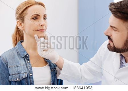 Chin surgery. Serious nice cosmetic surgeon holding his patients chin and looking at her face while preparing her to a cosmetic chin surgery