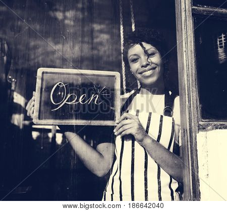 Woman Holding Open Sign by the Glass Window