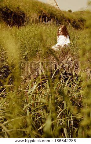Portrait of little Caucasian girl in white dress seating on old little stone bridge with the flute (Palmanova Friuli-Venezia Giulia Italy).