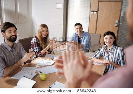 Feeling happiness. Group of coworkers looking at their friend clapping hands while sitting next to each other