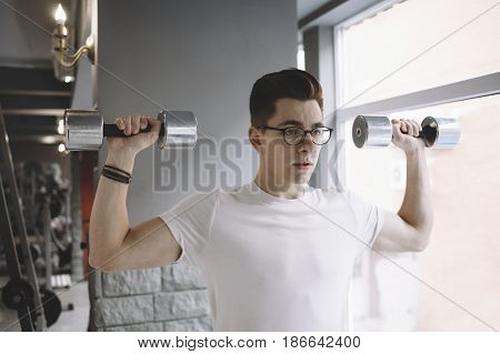 Tired and weary young sportsman training in the gym near big bright window with dumbbells holding it vertically and aside. Close up