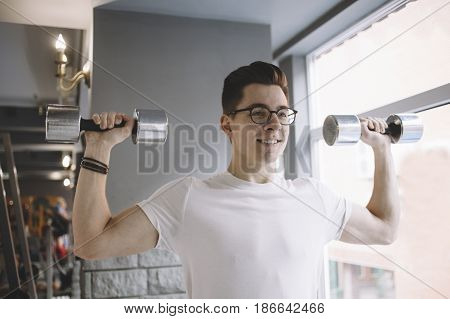 Young cheerful sportsman doing workout with dumbbells holding them up aside. Nice guy is smiling becaus soon he will have some rest. Close up