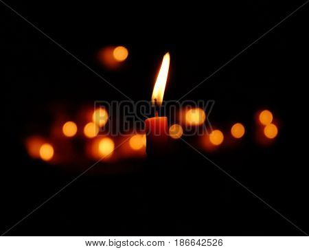 Candle light glowing in darkness with the bokeh background