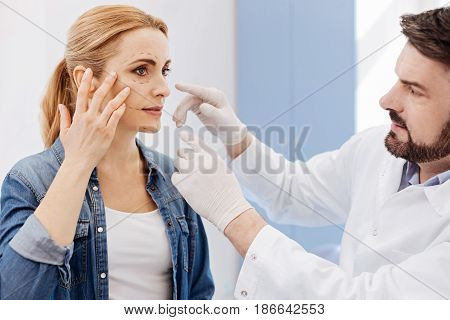 Pay attention here. Beautiful nice attractive woman pointing at her cheek and looking at her plastic surgeon while explaining him what she wants