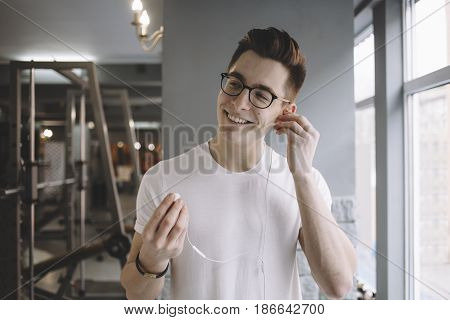 Young happy sportsman listening to music after doing workout with dumbbells. Attractive guy is smiling for having deserved rest. Close up