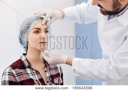 Plastic surgery clinic. Nice pleasant attractive woman sitting on the chair and wearing a cap and having a consultation with her plastic surgeon