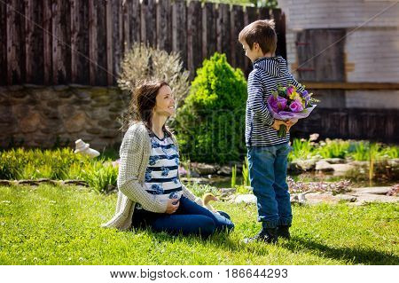 Young pregnant woman receiving bouquet of colorful flowers from her child for Mothers Day sitting in a beautiful spring blooming garden. Mother's day concept