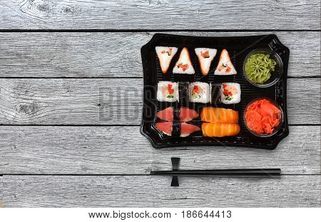 Japanese food delivery. Sushi and rolls top view with copy space on gray wood