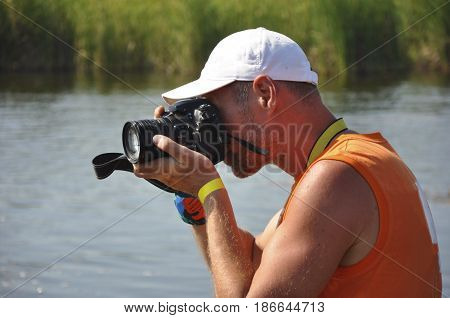 A white man photographing on SLR camera at the background of the river